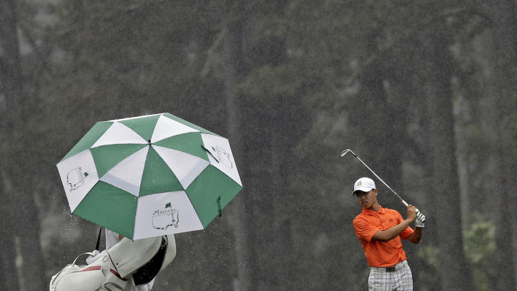 Amateur Guan Tianlang, of China, waits to hit on the eighth fairway in the rain during the second round of the Masters golf tournament Friday, April 12, 2013, in Augusta, Ga. (AP Photo/David J. Phillip)