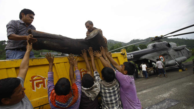 Locals unload a large piece of wood from a truck to be placed on to an Indian Air force helicopter as cremation efforts for those killed in landslides and monsoon floods are underway, in Gauchar, in northern Indian state of Uttarakhand, Tuesday, June 25, 2013. Truckloads of wooden logs and clarified butter were loaded onto air force transport planes and flown to the temple town of Kedarnath to conduct a mass funeral for the flood victims, an air force official said. (AP Photo/Rafiq Maqbool)