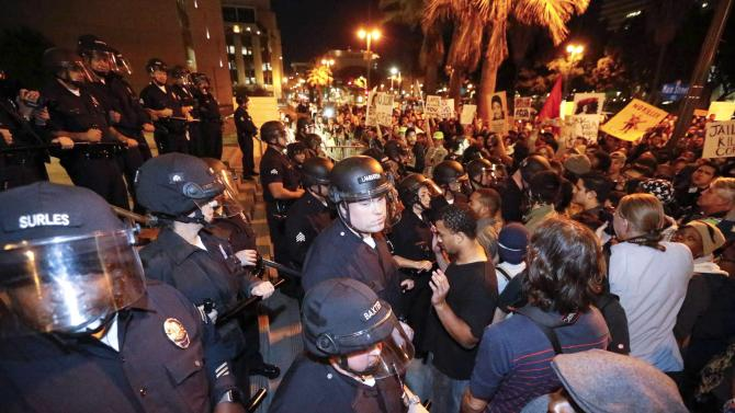 Protesters face off against a line of police during a demonstration outside LAPD headquarters, following the Monday grand jury decision in the shooting of Michael Brown in Ferguson, Missouri, in Los Angeles
