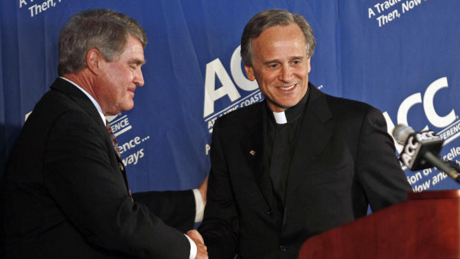 Notre Dame president Rev. John I. Jenkins, right, is congratulated by Atlantic Coast Conference commissioner John Swofford during a news conference at the University of North Carolina in Chapel Hill, N.C., Wednesday, Sept. 12, 2012. Notre Dame will play five football games annually against ACC schools, but will be a full member in all other sports.  (AP Photo/Gerry Broome)