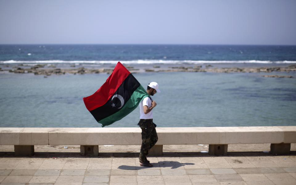 A man carrying a pre-Gadhafi Libyan flag walks on the sea front in at the rebel-held town of Benghazi, Libya, Friday, Aug. 19, 2011. (AP Photo/Alexandre Meneghini)