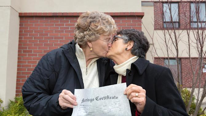 In this photo provided by Richard Wood, retired Army Col. Grethe Cammermeyer, left, kisses Diane Divelbess, her partner of 24 years, as they pose for photos after the two received their marriage license Thursday, Dec. 6, 2012, in Coupeville, Wash. Two retired military women who fought for the rights of gays in the military were among the hundreds of couples who received their marriage licenses this week as Washington state's voter-approved law allowing same-sex marriage took effect. Former Air Force flight nurse Maj. Margaret Witt, of Spokane, and Cammermeyer, of Whidbey Island, both successfully challenged the military's ban on open service by gays and lesbians. They were first in line on Thursday in their home counties to receive their licenses with their partners as the law took effect. (AP Photo/ kapchur.us photography, Richard Wood)