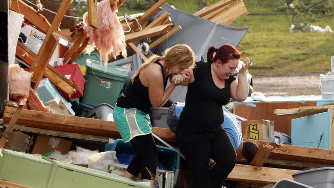 Alli Christian, left, helps Jessica Wilkinson as she looks for her dog Bella after Wilkinson returned to find her home near 156th street and Franklin Road destroyed by a tornado, Sunday, May 19, 2013, in Norman, Okla. (AP Photo/The Oklahoman, Steve Sisney)