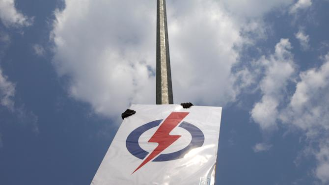 Worker puts up a People's Action Party (PAP) sign on a street lamp ahead of the general election in Singapore