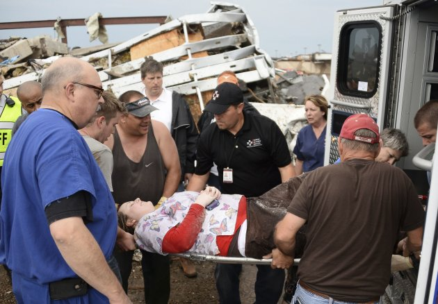 Rescue workers help one of 15 people rescued after being trap in a medical building at the Moore hospital complex after a tornado tore through the area of Moore