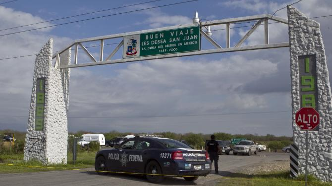 Federal policemen guard the area where dozens of bodies, some of them mutilated, were found on a highway connecting the northern Mexican metropolis of Monterrey to the U.S. border found in the town of San Juan near the city of Monterrey, Mexico,  Sunday, May 13, 2012. (AP Photo/Christian Palma)