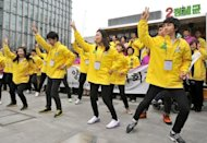 Volunteers of the main opposition Democratic United Party dance during an election campaign in Seoul, on March 29. Official election campaigns for the April 11 National Assembly elections began with over 900 candidates registered to compete for 246 parliamentary seats. Fifty-four seats are for proportional representatives