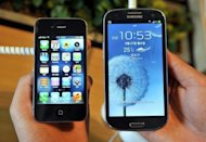 A store employee holds the Apple iPhone 4s (L) and a Samsung Galaxy S3 (R) in Seoul. Mobile gadgets powered by Google&#39;s Android software are devouring the market, eating into Apple&#39;s turf by feeding appetites for innovation and low prices, analysts say