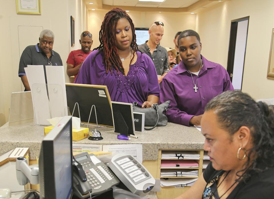 Rika Grier, left, and her partner Pastor Nicki Fairley, hear from Senior Assessment clerk Jennifer Samuela at the San Diego County marriage bureau while obtaining their license in San Diego, Monday, July 1, 2013. The pair have been together for six years. (AP Photo/Lenny Ignelzi)