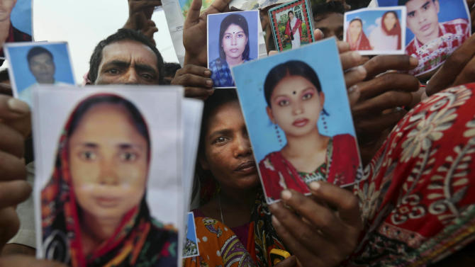 Bangladeshi relatives of workers missing in a building that collapsed Wednesday hold pictures of loved ones at a makeshift morgue in a schoolyard in Savar, near Dhaka, Bangladesh, Saturday, April 27, 2013. Police in Bangladesh arrested two owners of a garment factory in a shoddily-constructed building that collapsed this week, killing hundreds of people, as protests spread to a second city Saturday with hundreds of people throwing stones and setting fire to vehicles. (AP Photo/Kevin Frayer)
