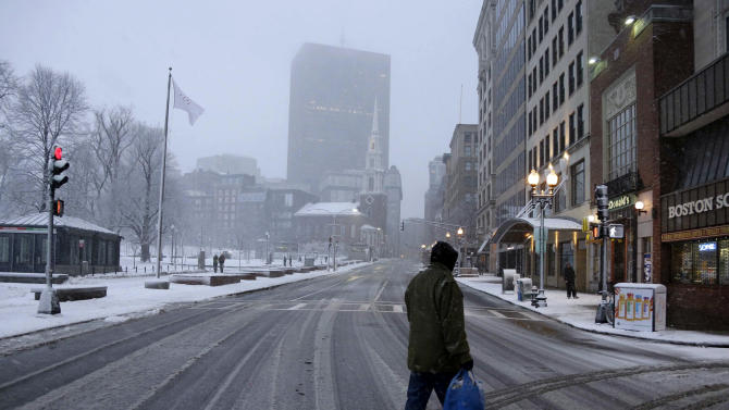 "A man crosses a traffic-less Tremont street in downtown Boston at rush hour, Friday, Feb. 8, 2013. Deval Patrick declared a state of emergency Friday and banned travel on roads as of 4 p.m. as a blizzard that could bring nearly 3 feet of snow to the region began to intensify. As the storm gains strength, it will bring ""extremely dangerous conditions"" with bands of snow dropping up to 2 to 3 inches per hour at the height of the blizzard, Patrick said.  (AP Photo/Gene J. Puskar)"