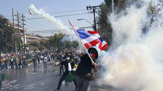 An anti-government protester throws back a tear gas canister fired by riot police in Bangkok, Sunday, Dec. 1, 2013. Riot police fired tear gas at anti-government mobs trying to force their way into the prime minister's office complex and Bangkok's police headquarters on Sunday, deepening Thailand's political crisis and raising fears of prolonged instability in one of Southeast Asia's biggest economies.(AP Photo/Wason Wanichakorn)