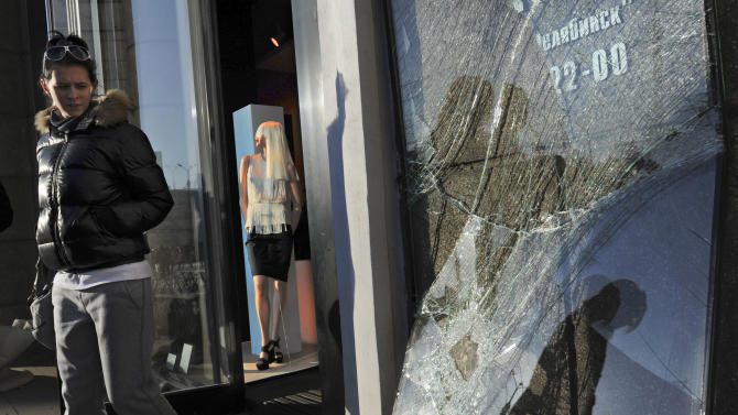A woman leaves a shop with a broken window in Chelyabinsk, Russia, on Monday, Feb. 18, 2013,  as part of the local damage after a meteorite exploded over the region on Feb. 15.  A total of 53 pieces of space debris have been brought for analysis to the university in Yekaterinburg, with the largest being about one centimeter in diameter, and the smallest is about one millimeter.  (AP Photo/Boris Kaulin)