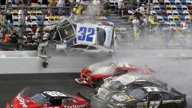Kyle Larson (32) goes airborne into the catch fence in a multi-car crash including  Dale Earnhardt Jr. (88), Parker Kilgerman (77), Justin Allgaier (31) and Brian Scott (2) during the final lap of  the NASCAR Nationwide Series auto race at Daytona International Speedway, Saturday, Feb. 23, 2013, in Daytona Beach, Fla. (AP Photo/John Raoux)