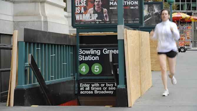 Plywood covers part of the entrance to Bowling Green Station in Battery Park as storm preparation is done, Sunday, Oct. 28, 2012, in New York. (AP Photo/ Louis Lanzano)