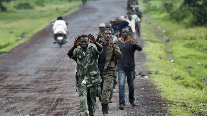 A column  of Congolese  M23 rebels  motion to the photographer not to take pictures  on the Goma to Rushuru road as they  look for FDLR (Force Democratique de Liberation du Rwanda) returning from an incursion into Rwanda Near Kibumba, north of Goma Tuesday Nov. 27, 2012. Speaking in Goma , M23 president Jean Marie Runiga said the rebels will not leave the city of 1 million which they seized a week ago. Rwanda military spokesman confirmed FDLR attacked Rwandan positions on Tuesday, which they repulsed and send back to Congo. (AP Photo/Jerome Delay)
