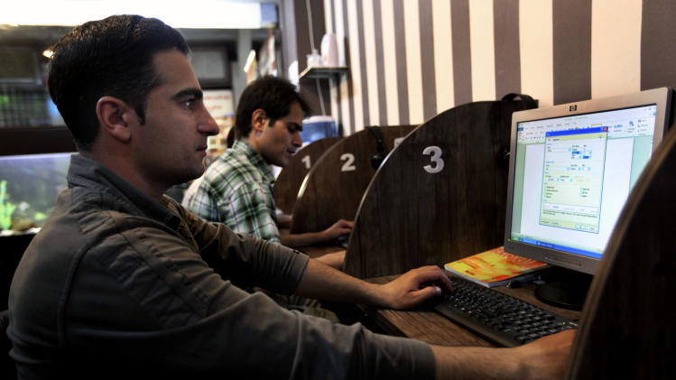 "FILE -- In this Monday, May 27, 2013 file photo, Iranians surf the web at an Internet cafe, in Tehran, Iran. Iranian authorities have restored blocks on Facebook and Twitter after a ""technical glitch"" briefly removed filters from the social networks overnight. The glitch could point to increasing internal struggles between groups seeking to reopen Facebook and other social networking sites and hard-liners in the establishment, who remain in control of Internet access. (AP Photo/Vahid Salemi, File)"