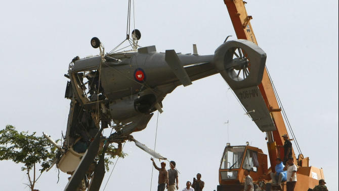 Soldiers use a crane to lift aft section of a helicopter retrieved from a pond following its crash in Prey Sar village at the outskirt of Phnom Penh, Cambodia, Monday, July 14, 2014. The chopper went down about 10 kilometers (6 miles) south of Phnom Penh on Monday, sinking in a muddy pond surrounded by rural land and rice fields. (AP Photo/Heng Sinith)