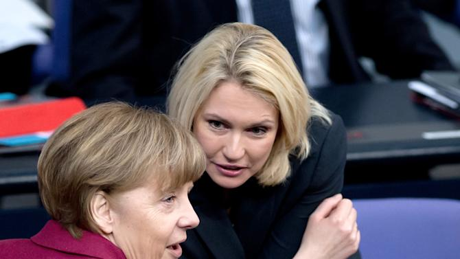 German chancellor Angela Merkel, left, and German Minister of Family Affairs Manuela Schwesig talk during a session of parliament in Berlin, Germany, Friday, March 6, 2015. Germany's Parliament has approved a quota system that will require leading companies in Europe's biggest economy to have at least 30 percent women on their supervisory boards starting next year. Lawmakers from Merkel's governing coalition backed the legislation Friday while opposition lawmakers who argued that it didn't go far enough abstained. (AP Photo/dpa, Soeren Stache)