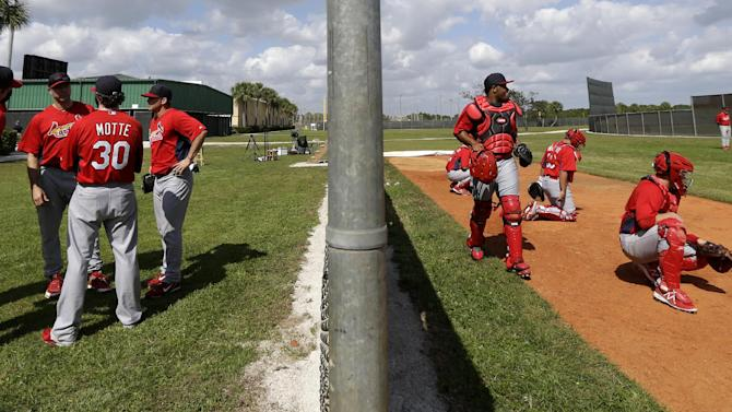 St. Louis Cardinals pitchers, left, gather as catchers work on a bullpen session during the team's first pitchers and catchers workout at spring training baseball, Tuesday, Feb. 12, 2013, in Jupiter, Fla. (AP Photo/Julio Cortez)