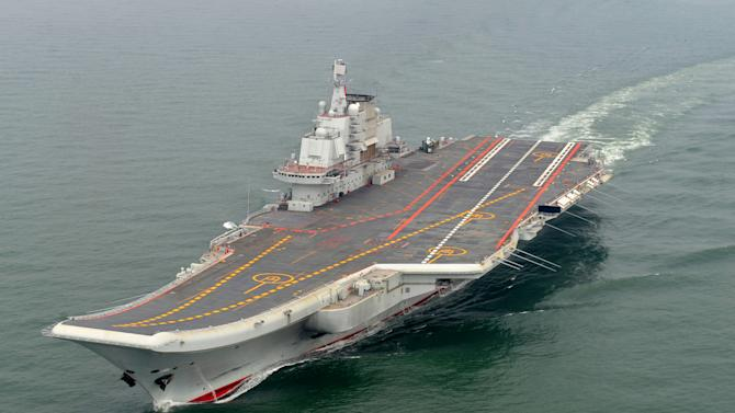 In this May 2012 photo provided by China's Xinhua News Agency, Chinese aircraft carrier Liaoning cruises for a test on the sea.  China formally entered its first aircraft carrier into service on Tuesday, Sept. 25, 2012, underscoring its ambitions to be a leading Asian naval power, although the ship is not expected to carry a full complement of planes or be ready for combat for some time. (AP Photo/Xinhua, Li Tang) NO SALES