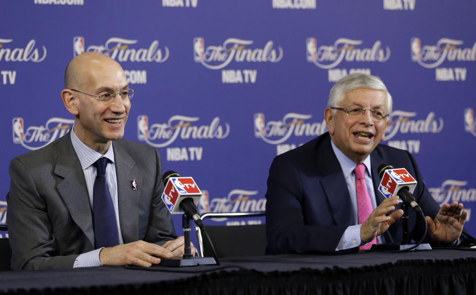 David Stern, NBA Commissioner, right, and Adam Silver, Deputy Commissioner, speak before the start of Game 1 of the NBA Finals basketball game between the San Antonio Spurs and Miami Heat, Thursday, June 6, 2013 in Miami. Silver will take over as NBA Commissioner when Stern retires February 1, 2014. (AP Photo/Wilfredo Lee)