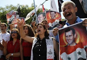 Protesters hold portraits of Syrian President Bashar…