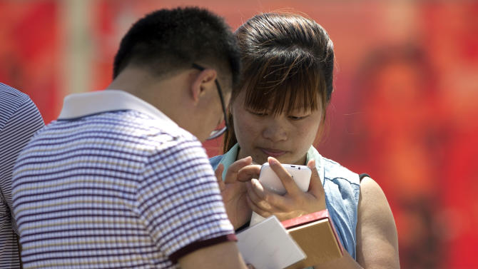 """Chinese people use their smartphone on Tiananmen Square in Beijing, China Wednesday, May 28, 2014. China is targeting popular smartphone-based instant messaging services in a month-long campaign to crack down on the spreading of rumors and what it calls """"hostile forces at home and abroad,"""" the latest move to restrict online freedom of expression. (AP Photo/Andy Wong)"""