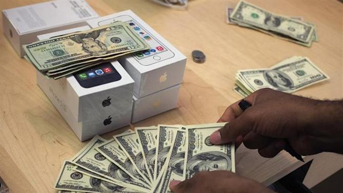 A cashier counts U.S. dollars next to five new Apple iPhone 5S phones at the Apple Retail Store on Fifth Avenue in Manhattan, New York September 20, 2013.