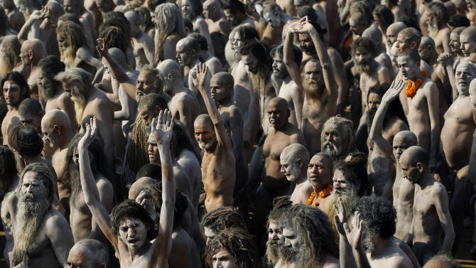 Indian Hindu holy men, some covered in ash, walk in procession after bathing at Sangam, the confluence of the Ganges, Yamuna and mythical Saraswati River, during the Maha Kumbh festival, in Allahabad, India , Sunday, Feb. 10, 2013. Millions of Hindu pilgrims are attending the Maha Kumbh festival, which is one of the world's largest religious gatherings that lasts 55 days and falls every 12 years. During the festival pilgrims bathe in the holy Ganges River in a ritual they believe can wash away their sins.  (AP Photo/Kevin Frayer)