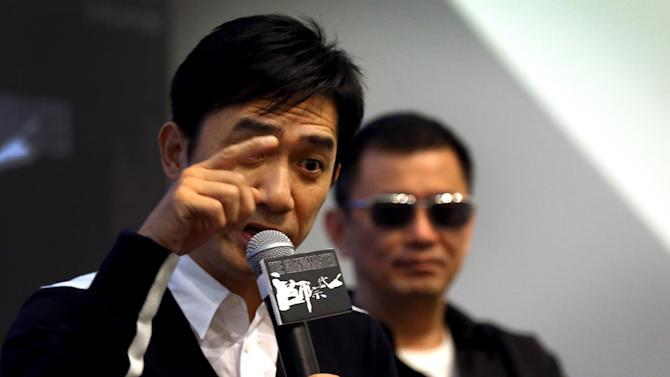 """Movie director Wong Kar-wai, right, watches from the background as Tony Leung, left, speaks during a press conference on Wednesday, Jan. 23, 2013 in Singapore. For a director and actor who have worked together for about two decades, there did not seem to be much chemistry between Wong and Leung at the news conference promoting their new movie """"The Grandmaster."""" (AP Photo/Wong Maye-E)"""