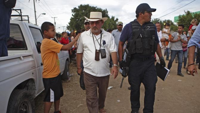 Vigilante leader Hipolito Mora and other vigilantes walk with their family and friends to voluntarily cooperate in a shootout investigation in La Ruana, Michoacan