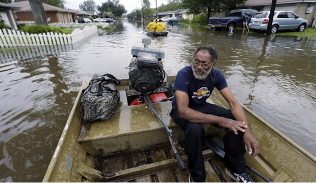 Milton is taken by boat from a flooded neighborhood, Thursday, Aug. 30, 2012, in Reserve, La. Isaac soaked Louisiana for yet another day and pushed more water into neighborhoods all around the city, f