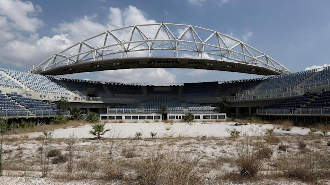 In this Friday, Aug. 8, 2014 photo, the abandoned beach volleyball Olympic venue is seen in Neo Faliro, southern Athens. As Greece groans under a cruel depression, forecast to end this year, the 10-year anniversary once again raises the question of whether the Athens Games were too costly an undertaking for a weak economy. (AP Photo/Thanassis Stavrakis)