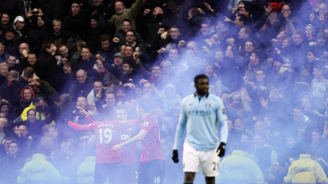 Manchester United's Robin van Persie, 2nd left, is shrouded in smoke as he celebrates with teammates after scoring the winning goal against Manchester City during their English Premier League soccer match at The Etihad Stadium, Manchester, England, Sunday Dec. 9, 2012. United won the match 3-2.  (AP Photo/Jon Super)