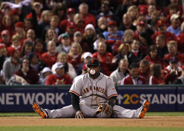 San Francisco Giants third baseman Sandoval sits on the ground after making a diving stop but was late on the throw to get St. Louis Cardinals Craig at first in the seventh inning during Game 4 of the