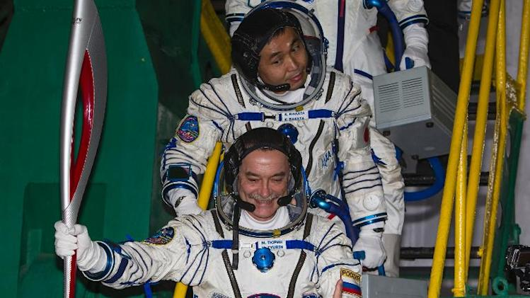 Japanese astronaut Koichi Wakata (top) and Russian cosmonaut Mikhail Tyurin pose with the Sochi 2014 Winter Olympic torch as they board prior to blast off to the International Space Station in Kazakhstan on November 7, 2013