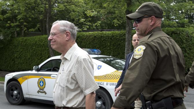 Rail World Inc. president Edward Burkhardt is escorted by police as he tours Lac-Megantic, Que., on Wednesday, July 10, 2013. A Rail World oil train derailed in the town killing at least 15 people. (AP Photo/The Canadian Press, Paul Chiasson)