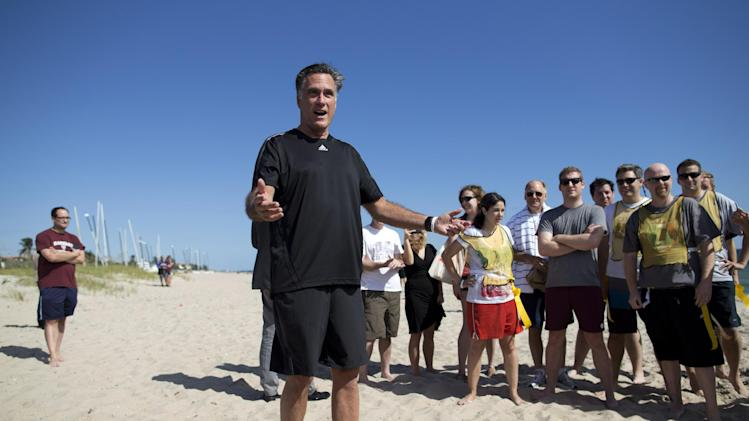 Republican presidential candidate, former Massachusetts Gov. Mitt Romney speaks before the start of a flag football game between between reporters that cover Romney, and Romney staff on Sunday, Oct. 21, 2012 in Delray Beach, Fla.  Romney took a short break from debate preparations to do the opening coin toss, and watch the first play of the game.  (AP Photo/ Evan Vucci)