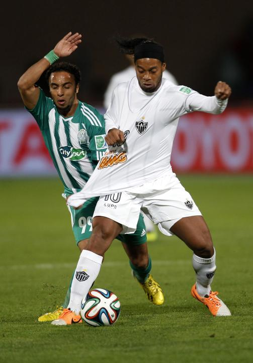 Raja Casablanca's Issam Erraki fights for the ball with Atletico Mineiro's Ronaldinho during their FIFA Club World Cup semi-final soccer match at Marrakech stadium
