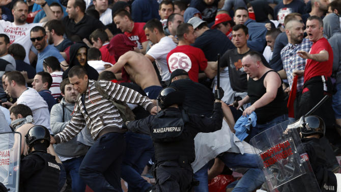 Serbian riot police officers clash with Red Star soccer fans during a Serbian National soccer league derby match between Red Star and Partizan, in Belgrade, Serbia, Saturday, April 25, 2015. Thousands of riot policemen have been deployed throughout Belgrade to prevent possible violence during a derby match between bitter rivals Red Star and Partizan. (AP Photo/Darko Vojinovic)