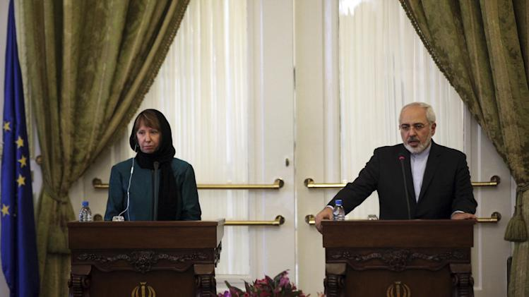Iranian Foreign Minister Mohammad Javad Zarif, right, speaks in a joint press briefing with the European Union's foreign policy chief Catherine Ashton after their meeting, in Tehran, Iran, Sunday, March 9, 2014. Ashton is saying there is no guarantee for a successful final nuclear deal with Iran. (AP Photo/Vahid Salemi)