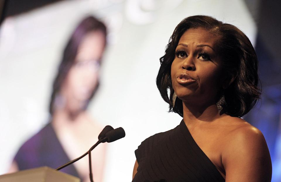 First lady Michelle Obama, and her image displayed on a video screen behind her, addresses the Congressional Black Caucus Foundation's 42nd Annual Phoenix Awards dinner in Washington, Saturday, Sept. 22, 2012. (AP Photo/Cliff Owen)