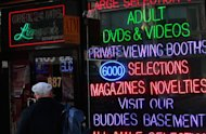 A man passes by an adult video store January 8, 2009 in New York. US porn filmmakers sued Los Angeles County over a new law requiring adult movie actors to wear condoms on set, arguing that it is unconstitutional