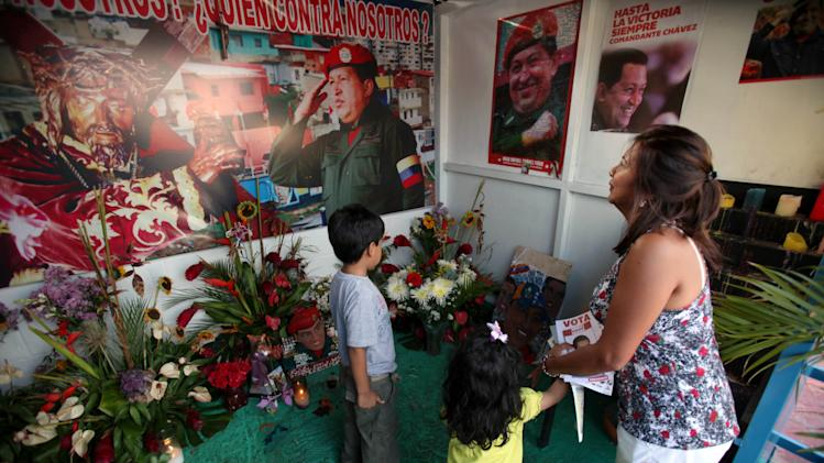 "A woman and her two children visit a people's shrine built in honor of late Venezuela's President Hugo Chavez at the ""23 de Enero"" or ""23rd of January"" slum in Caracas, Venezuela, Wednesday, April 3, 2013. The shrine, named  ""Saint Hugo Chavez del 23"", has been visited by tens of thousands of Venezuelans to pay homage to a president for some, a saint for others. (AP Photo/Fernando Llano)"