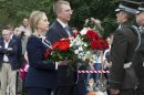 U.S. Secretary of State Hillary Rodham Clinton pays her respects at the Freedom Monument with Latvian Foreign Minister Edgar Rinkevics in Riga