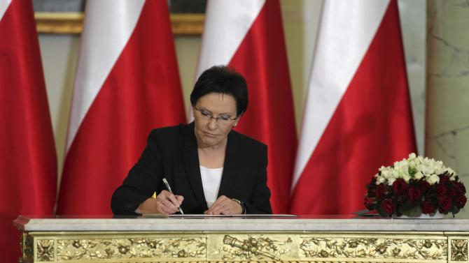 Kopacz signs documents as she is sworn in as the new Polish PM during a ceremony at the Presidential palace in Warsaw