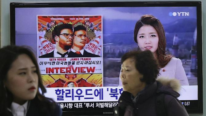 """FILE - In this Dec. 22, 2014 file photo, people walk past a TV screen showing a poster of Sony Pictures Entertainment's """"The Interview"""" in a news report at the Seoul Railway Station in Seoul, South Korea. Sony's iconic gadgetry and the star appeal of Hollywood may have appeared to be a perfect match when the electronics giant bought Columbia Pictures in 1989. A quarter century later, it's apparent that Sony Corp. has not attained the magic synergy it was hoping for. The stolid silence of Sony's Tokyo headquarters over the hoopla surrounding """"The Interview"""" underscores the longstanding divide between the Japanese parent company and its U.S.-led and -run motion pictures subsidiary, successor to Columbia Pictures.  (AP Photo/Ahn Young-joon, File)"""