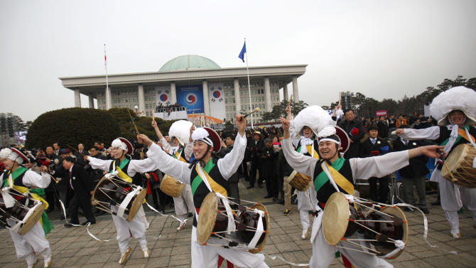 """Members of a """"Samulnori"""" dance troupe, or traditional South Korean percussion quartet, perform during the inauguration of South Korea's new President Park Geun-hye, not pictured, at parliament in Seoul, South Korea, Monday, Feb. 25, 2013. Elected in December, Park is believed to be the first Korean woman to rule in a millennium. (AP Photo/Kim Hong-Ji, Pool)"""