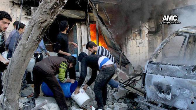 In this citizen journalism image provided by Aleppo Media Center (AMC), an anti-Bashar Assad activist group, and authenticated based on its contents and other AP reporting, Syrian citizens fill water in a bucket to extinguish shops in flames caused by a Syrian government forces warplane attack, at al-Bab neighborhood in Aleppo, Syria, Saturday, Feb. 1, 2014. Syrian military helicopters dropped barrels packed with explosives on rebel-held areas of the northern city of Aleppo on Saturday, killing at least a dozen of people including a family trapped in a car, as government forces inched closer to opposition-held areas. (AP Photo/Aleppo Media Center, AMC)
